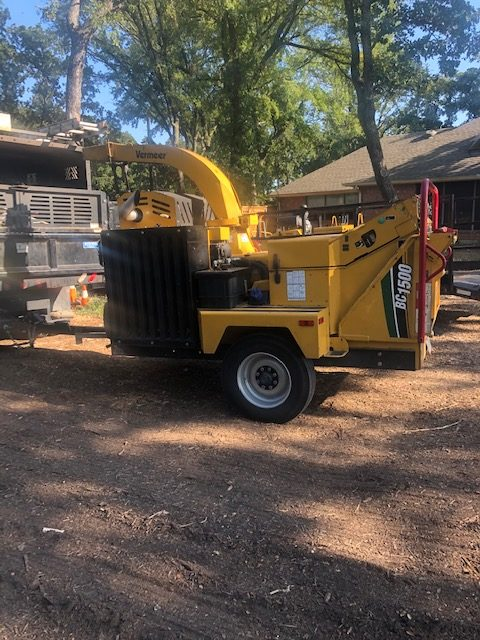 a branch and tree grinder parked in front of a home in Keller Texas